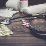 statoscope and pills over brown wooden table