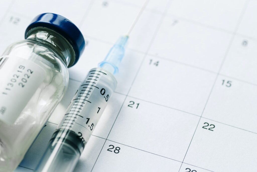 The vial with vaccine and syringe on calendar